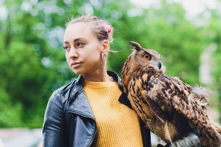 The owl sits on the girls hand. The woman with the owl.