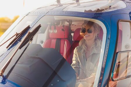 Upbeat mood. Beautiful helicopter pilot smiling cheerfully while listening to air traffic controller in her headphones. Standard-Bild