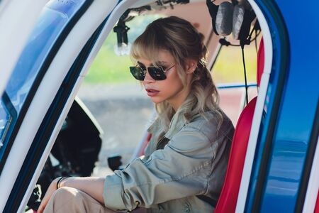 Upbeat mood. Beautiful helicopter pilot smiling cheerfully while listening to air traffic controller in her headphones. Reklamní fotografie