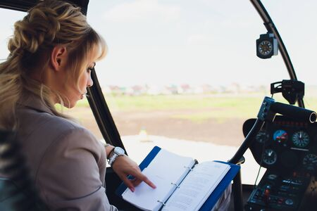 Female pilot in cockpit of helicopter before take off. Young woman helicopter pilot. Banco de Imagens
