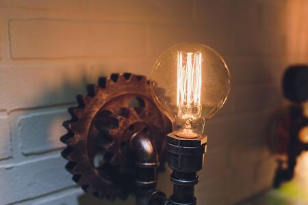 Steampunk architectural style design element of interior. Lamp bulbs fixed on iron industrial gear cogwheels sprocket lighting illuminated equipment hanging indoors.