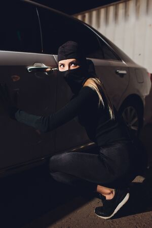 Masked robber woman car The thief is levering the lock at the door car robbery.