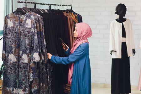 Une femme arabe en vêtements musulmans traditionnels achète une nouvelle robe dans un magasin oriental.
