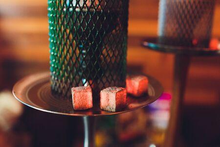 Prozess der Herstellung von Wasserpfeifen zum Rauchen. Konzept, eine Wasserpfeife zu rauchen und eine gute Zeit zu haben. Shisha Bowl auf dem dunklen Hintergrund der Bar Nahaufnahme. Getöntes Bild.