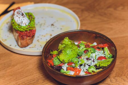 Vegetable salad with avocado, cucumber, cherry tomato, chard leaves and broccoli on a plate, on the wooden table.