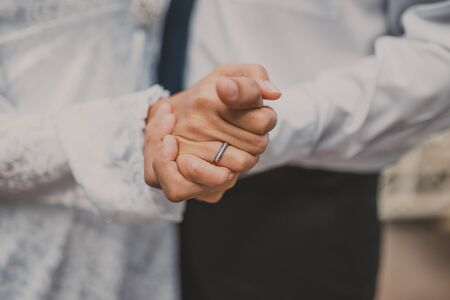 Close-up of grooms hand holding brides wirst tender. Stock Photo