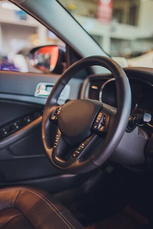 Dark luxury car Interior - steering wheel, shift lever and dashboard. Car interior luxury. Beige comfortable seats, steering wheel, dashboard, climate control, speedometer, display, light wood panels.