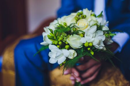 groom holding a bouquet green behind close-up. Stock Photo