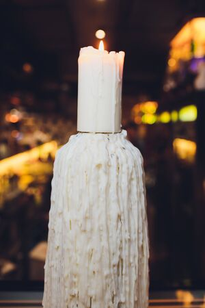 closeup of a burning candle on a dark background with soft lighting. Stock Photo