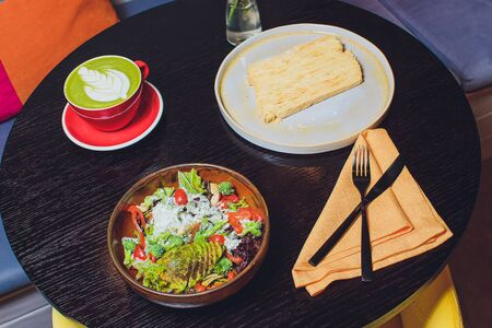 A set lunch of Japanese on a table in a restauran, include grill salmon, rainbow salad, green soy bean, matcha tea.