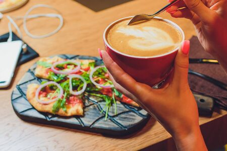 partial view of woman sitting at table with pizza piece on plate and cup of coffee. Stock Photo