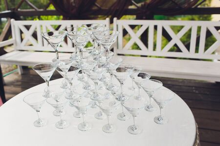 Empty wine or champagne glasses on table are in pyramid.