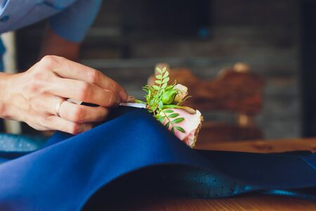 hand clings to the bridegroom a boutonniere of real flowers.