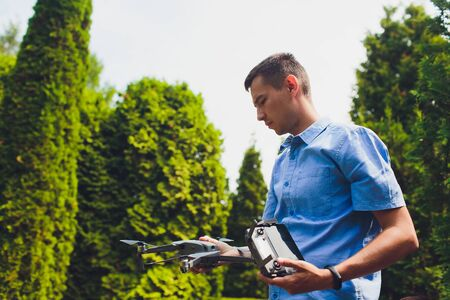 man and his drone, quadrocopter in a forest on a green background.