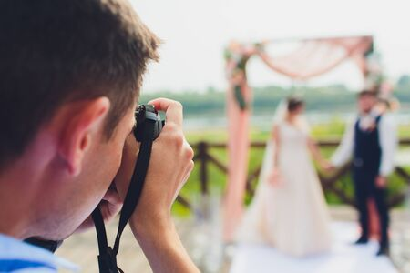 wedding photographer takes pictures of bride and groom in city. wedding couple on photo shoot. photographer in action. Stock Photo