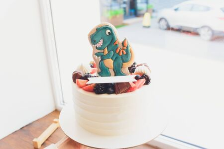 Childrens holiday white cake decorated with mastic figurines of dinosaurs in the Jurassic period jungle. Concept ideas desserts for kids Imagens