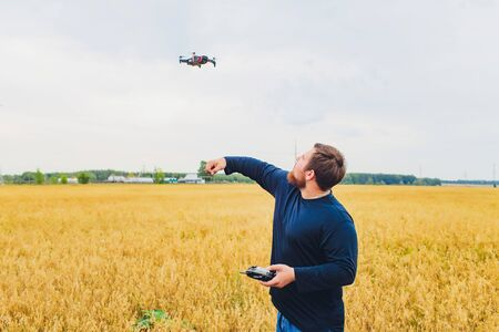 Farmer holds remote controller with his hands while quadcopter is flying on background. Drone hovers behind the agronomist in wheat field. Agricultural new technologies and innovations. Back view. 写真素材
