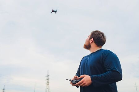 Farmer holds remote controller with his hands while quadcopter is flying on background. Drone hovers behind the agronomist in wheat field. Agricultural new technologies and innovations. Back view. Zdjęcie Seryjne