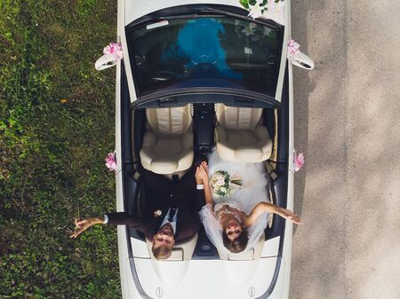 Happy bride kiss groom, newlywed wedding couple is driving a convertible retro car with balloons on a country road for honeymoon after the ceremony. Way. The best day and marriage. Just married.