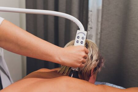 Cropped view of cosmetologist with roller doing buttocks starvac massage.