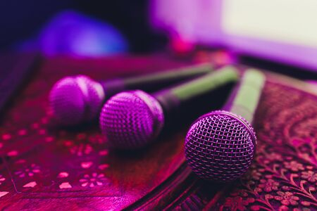 three Microphones in group on red table with copy space. Stok Fotoğraf