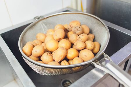 Young, small, whole fried potatoes. Golden fried. With garlic and greens.