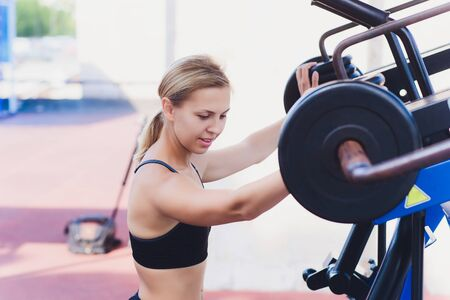 Profile view of a female athlete doing some tricep dips on a park bench.