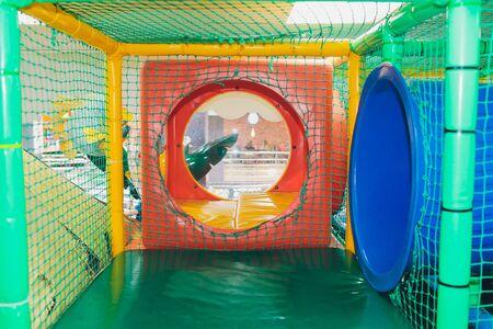 Modern playground indoor. Kids jungle in a play room. Round tunnel in children gym. Standard-Bild - 131911237