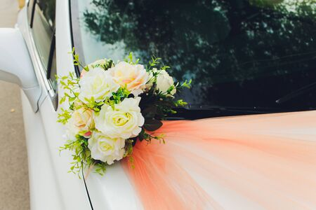 Wedding bouquet bridal decoration on luxury white car.