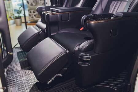 close-up of the black leather rear seats with footrest. modern car interior. Stockfoto