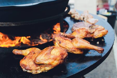 Chicken Leg Quarters on Barbecue Grill street food.