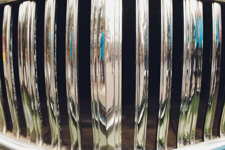 Shiny chromed front radiator grill of classic luxury car.