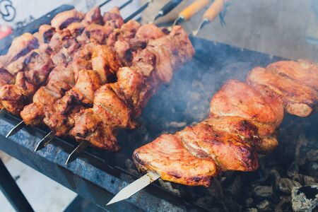 Grilled kebab cooking on metal skewer. Roasted meat cooked at barbecue. BBQ fresh beef meat chop slices. Traditional eastern dish, shish kebab. Grill on charcoal and flame, picnic, street food.