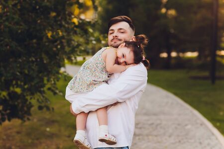 Fatherhood, family and leisure concept - father holding little daughter in his arms in park. 写真素材