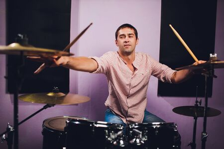 Young man behind drum-type installation in a professional recording studio.
