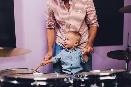 little boy plays drums in recording studio. Фото со стока