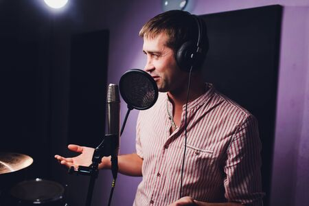 music, show business, people and voice concept - male singer with headphones and microphone singing song at sound recording studio.