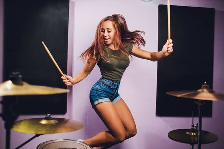 Photograph of a female drummer playing a drum set on stage.