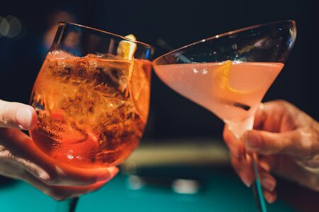 Hands of man and woman cheering with glasses of pink champagne.