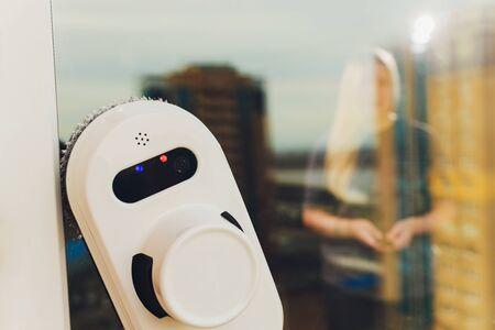 Vacuum cleaner robot cleaning window in high building outdoor. Stok Fotoğraf