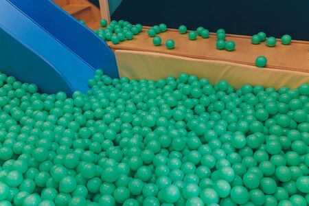 Top view on lot of plastic green balls in playground pool.