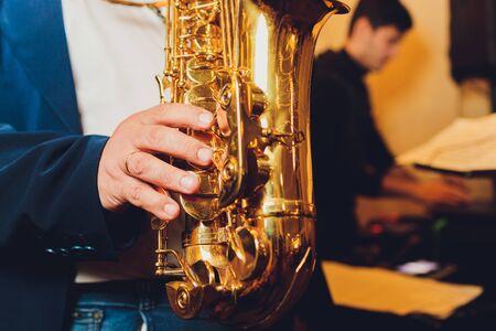 Instrument de musique classique saxophone Saxophoniste avec gros plan sax alto sur noir. Banque d'images