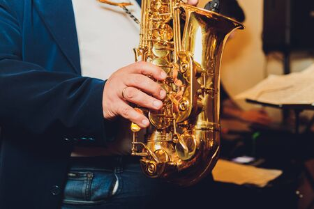 Saxophone classical music instrument Saxophonist with alto sax closeup on black.