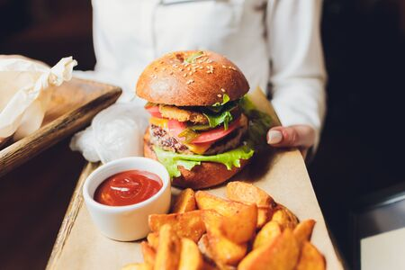 fresh tasty burger and french fries on wooden table.