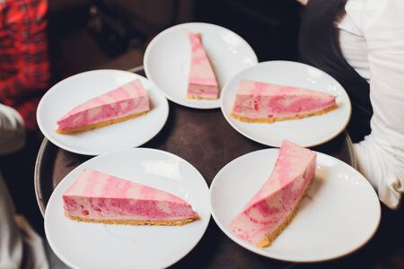 portion of a white chocolate raspberry cheesecake on a plate and sliced cheesecake on a black stone tray with cloth and frozen raspberries on a white wooden table, view from above, close-up.