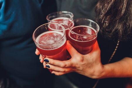 Woman holding three glasses of red beer. Stockfoto