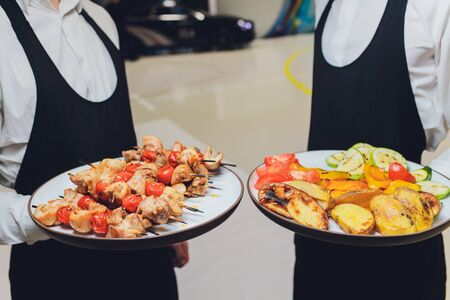 Serving hot shish kebab with vegetables and sauce in a restaurant
