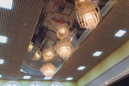 white lightning balls. modern art luxury chandelier made with balls with lamp inside every one, which conncet to beautiful flower with silver legs. Lighting ball hanging from the ceiling on background. Banco de Imagens