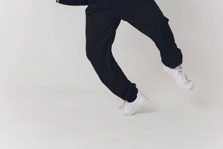 Close-up, Handsome young dancer dressed in black pants, a sweatshirt on a naked torso lifts one leg up while dancing street dance. Stock Photo