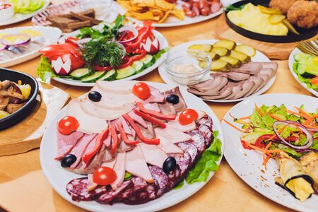 Food tray with delicious salami, pieces of sliced ham, sausage and salad. Meat platter with selection on table Stock Photo - 131357894